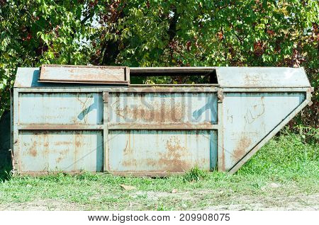 Old grunge metal dumpster can for garbage with rusty spots on the green grass surface in the city park