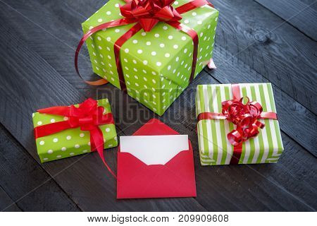 Bunch of colorful presents wrapped in paper and tied with red ribbon and bows with an opened envelope and blank paper on an old wooden table.