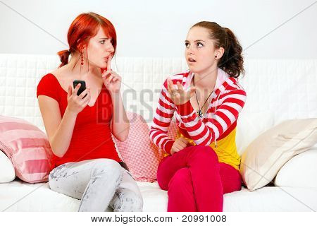 Young girl with mobile showing silence gesture her indignant girlfriend