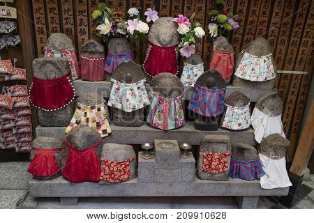 Kyoto - Japan, May 22, 2017: Traditional stone carved Jizo with different colored skirts in front of the temple for praying and wishing