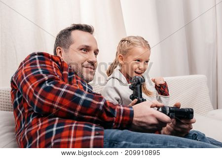Father And Daughter Playing With Joysticks