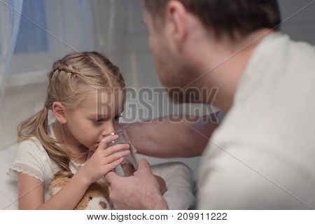 Father Giving Water To Daughter In Bed