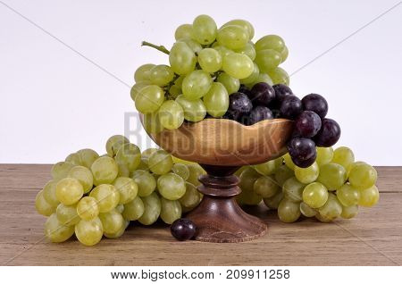 clusters of grapes of different varieties in a wooden bowl