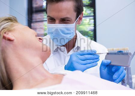Close up of dentist showing equipment to patient at medical clinic