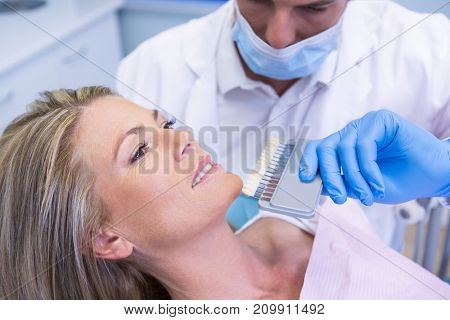 High angle view of dentist holding equipment while examining patient at medical clinic