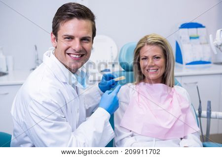 Portrait of doctor holding dental mold while sitting by patient at clinic