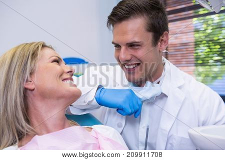 Cheerful patient looking at dentist while sitting on chair at dental clinic