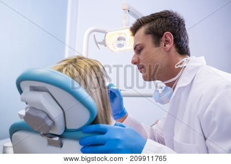Side view of dentist polishing woman teeth at dental clinic