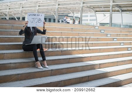business woman unemployed from company sitting on the staircase and holding poster with text is looking for job concept of unemployment problem