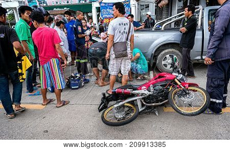 BANGKOK THAILAND - OCTOBER 14: Rescue Workers get to work to assist a man in a motorcycle traffic accident while surrounded by onlookers in Bangkok on October 14 2017.