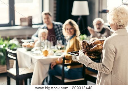 senior woman carrying thanksgiving turkey for holiday dinner with family