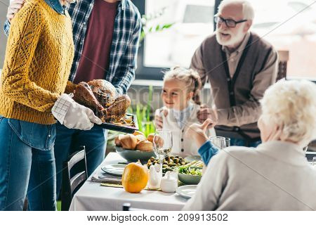 cropped shot of man and woman carrying turkey for thanksgiving dinner while excited family looking at it