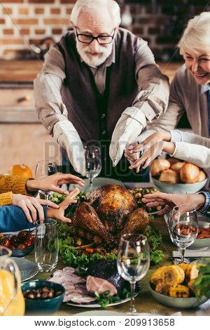 grandparents and family reaching for turkey on holiday table