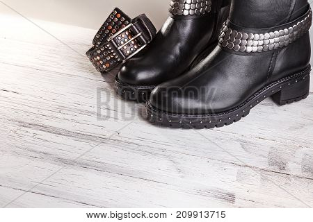 A pair of black leather boots with belt on a thick soles lie on a white wooden background. Trendy women's boots for the winter. Fashionable women's brown leather boots.