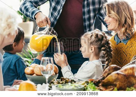 father pouring orange juice for daughter at holiday dinner