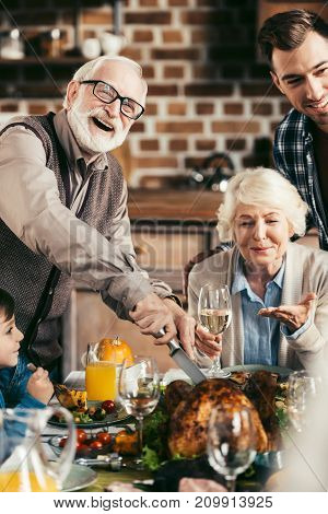 happy excited family cutting thanksgiving turkey while celebrating