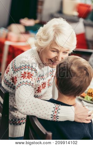 Grandmother And Grandson Talking At Christmas Table