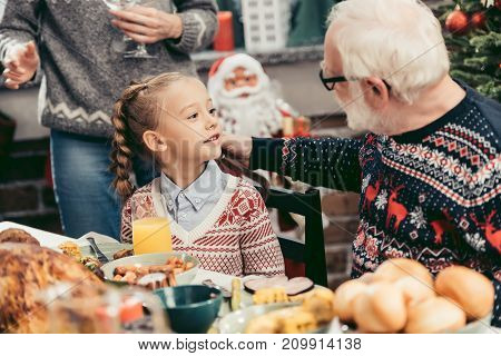grandfather and beautiful little granddaughter talking at christmas table
