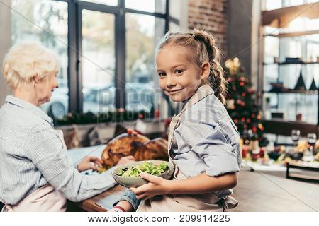 Granddaughter Assisting For Grandmother On Kitchen