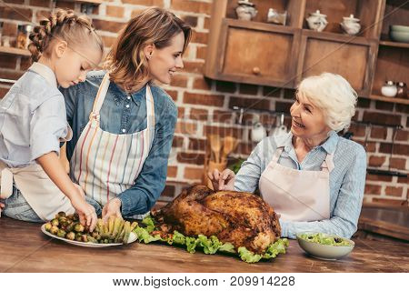 beautiful women of three generations preparing dishes for thanksgiving dinner