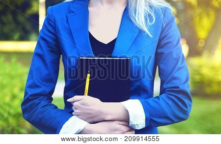 Book in hands of young student in park