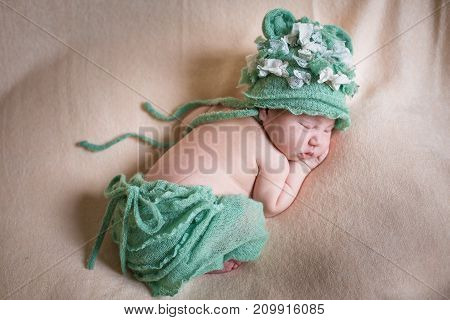 Sleeping newborn baby girl in a green knit panties and hat. Sleeping on a covered sheet.