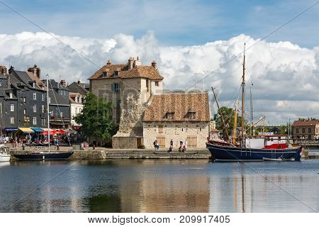 HONFLEUR, FRANCE - AUGUST 24, 2017: Harbor of historic city Honfleur with moord sailing ships. An impressive cloud bank is approaching the city