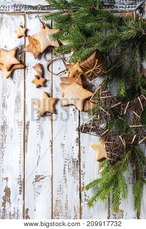 Garland of homemade shortbread star shape sugar cookies different size on thread with sugar powder, toys, fir branch over white wooden plank surface. Christmas treat background. Top view with space