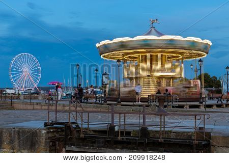 HONFLEUR, FRANCE - AUGUST 24, 2017: Caroussel and ferris wheel at the harbor of Honfleur. Long exposure image in the evening with rotating carrousel