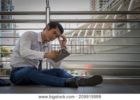 businessman unemployed from company sitting on the street and use tablet for find a new job concept of business failure and unemployment problem