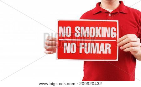 a man holding a Spanish no smoking sign.