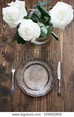 Romantic table setting with vintage dishware, silverware and decorations on wooden board. Top view. Selective focus.