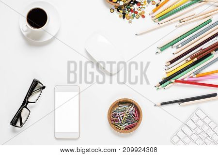 Top view of messy white office desk with colorful supplies empty smartphone coffee cup and other items. Close up mock up