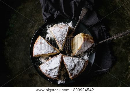 Sliced homemade pie with custard and sugar powder on black plate with vintage fork, textile napkin over old dark metal background. Top view. Rustic style
