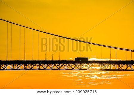 Truck crossing suspension bridge at sunset. Forth Road Bridge in North Queensferry Scotland