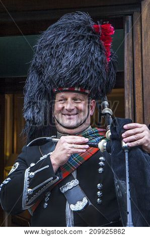 Edinburgh Scotland - March 6 2010: Bagpiper smiling. Edinburgh the most popular tourist city destination in Scotland