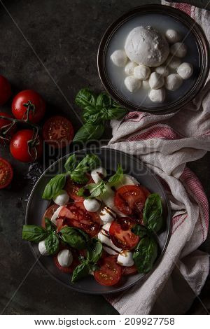 Italian caprese salad with sliced tomatoes, mozzarella cheese, basil in vintage metal plate with ingredients above over dark metal background. Top view with space. Rustic style. Toned image