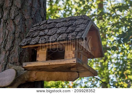 Wooden house for birds with original roof close-up.