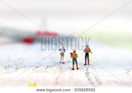 Miniature Group traveler with backpack standing on wold map and walking to airplane on world map with copyspace for travel around the world. Travel Concept select focus