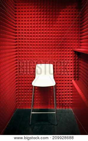 white stool in a red cabin with foam soundproof panels