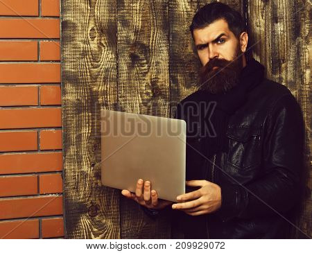 Bearded Brutal Caucasian Hipster Holding Tablet And Laptop