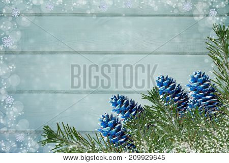 Snow-covered Fir Branches And Blue-colored Cones On Light Green Painted Wooden Boards Backgrounds Wi