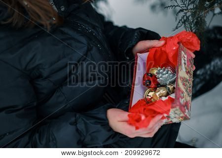 Box with glass Christmas tree toys. Gift in a red box. The child holds an open gift in his hands.