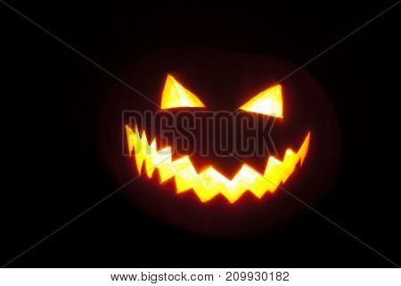A pumpkin lantern brightly glowing from the inside on a black background