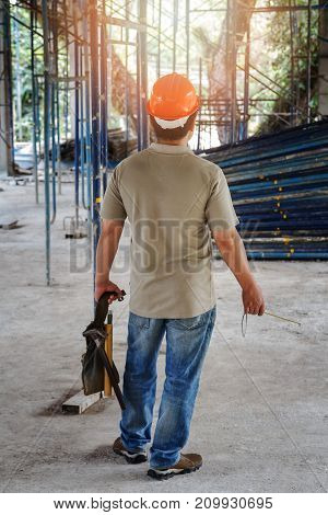 Worker Holding Tool Bag In Building Construction Site