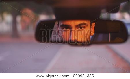 Serious young man driving car and looking at camera through back mirror