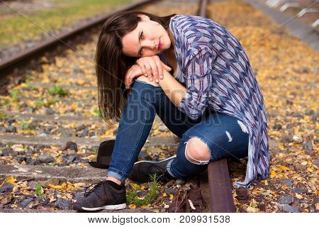portrait of beautiful young woman sitting on train tracks and looking sad