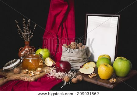 Autumn still life honey and apples on a wooden board, nuts in a bag and dry lavender in a clay vase on a red-black background