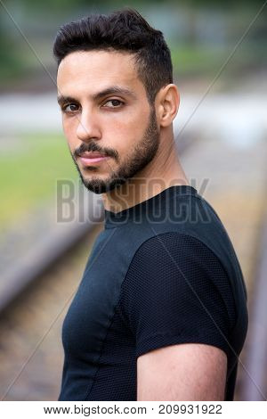 portrait of handsome young man standing outside next to train tracks
