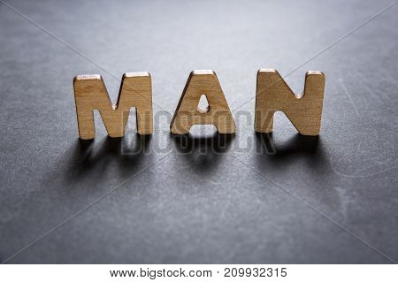 Word Man Of Wooden Letters On A Dark Texture With A Black Background With Backlight. Lighting Effect